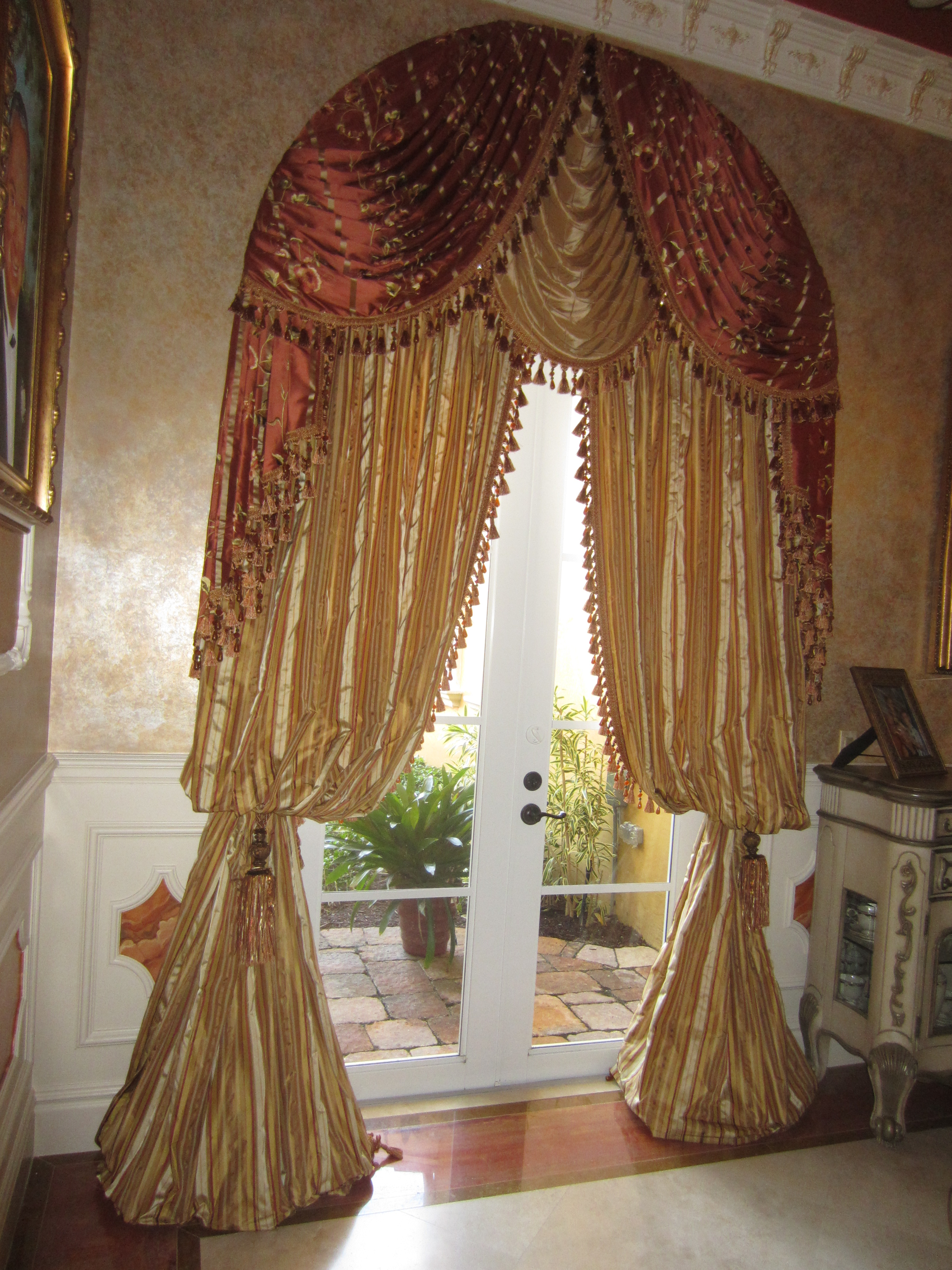 Swags & Jabots w/ Beaded Tassel Fringe over Stationary Panels in a Bishops Sleeve w/ Rope Tiebacks on an Arch Window